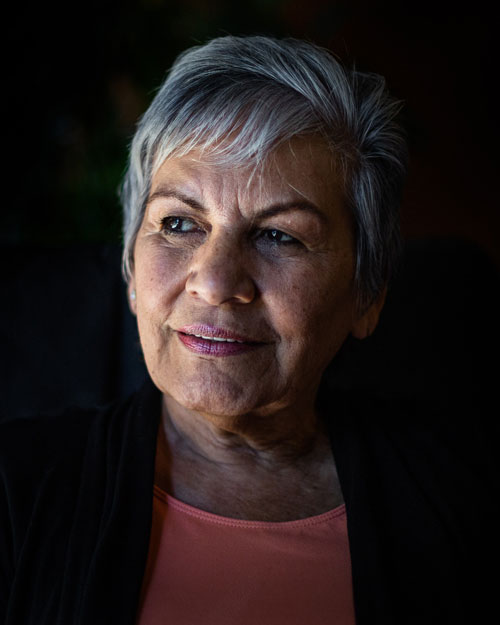Older woman with short gray hair is smiling in a cloud of black. She is wearing a pink shirt and is looking into the distance where a light is cominf from. This pictures is being used as the feature image for Senior Scholars program.