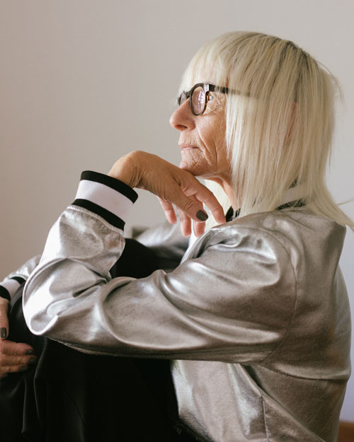 Picture of an older woman sitting facing the left. Right hand hugging her knee and left hand under her chin. This picture is being used as the feature image for the OSher Lifelong Learning Institute(OLLI).